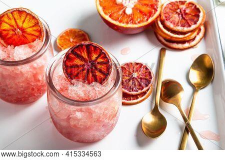 Homemade Italian Granita Dessert With Blood Orange, Elderflower, Rose Wine  In Serving Glasses On A