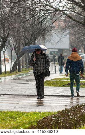 Timisoara, Romania - January 20, 2014: Man With Umbralla Walking On The Street. Real People.