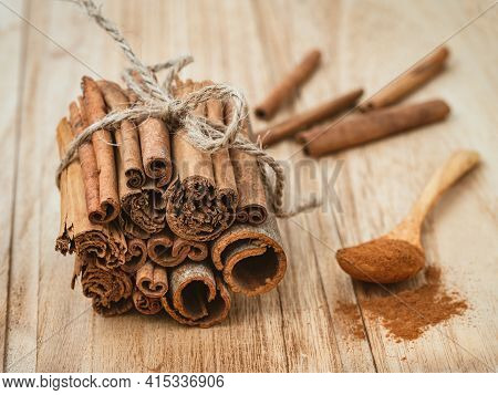 Cinnamon Sticks Tied In A Log And Ground Cinnamon In A Wooden Spoon.