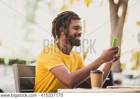 Photo Portrait Of Guy With Dreadlocks Sitting Outside Cafe Browsing Internet Typing Sms On Mobile Ph