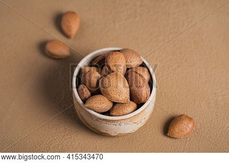 Pile Of Almond Nuts In A Bowl On A Brown Background. Fresh Nuts In Their Shells.
