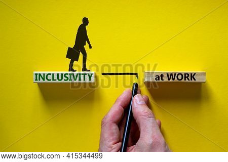 Inclusivity At Work Symbol. Wooden Blocks With Words 'inclusivity At Work' On Beautiful Yellow Backg