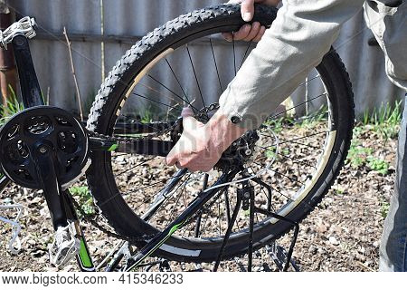 A Man Dismantles The Rear Wheel Of A Bicycle Outdoors.