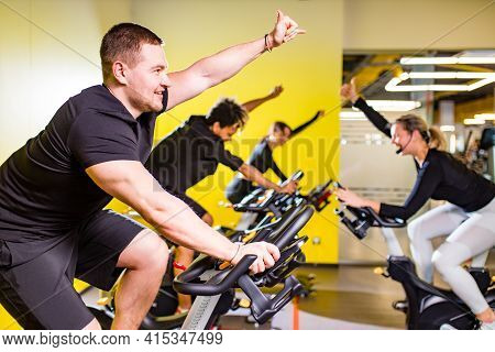 Pretty Authentic Female Instructor With Headset In Fitness Class Exercise With Group In Cycling Room