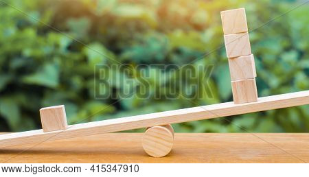 One Wooden Block On The Scales Outweighs The Other Four. Inequality Concept. One Against The Others.