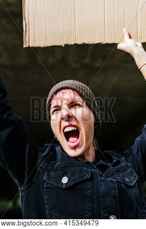 Androgynous-looking Young Girl Screaming Enraged At A Demonstration. Person Holding A Cardboard Sign