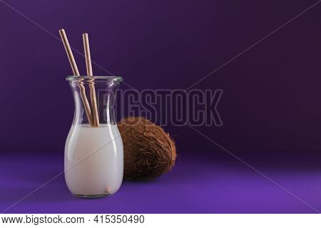 Bottle Of Coconut Vegan Milk With Straws And Whole Coconut On Purple Background. Healthy Lifestyle C