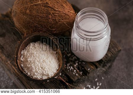Coconut, Coco Flakes And Coconut Oil In Jar On Dark Background. Healthy Cooking Concept