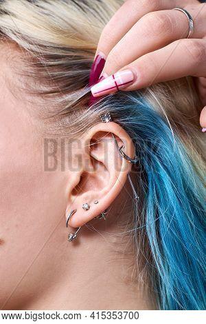 Deer Stud Earring On Womans Ear Close Up. Piercing