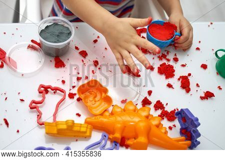 A Childs Hands Play With Bright Kinetic Sand On A White Table. An Educational Game Of Kinetic Sand W