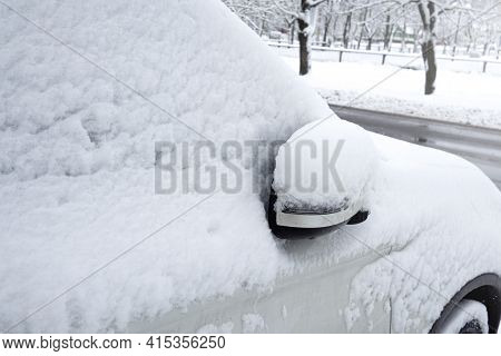 Car Covered With Snow In The Winter Blizzard In The Parking Lot