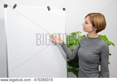 A Young Woman Is Standing In A Bright Room Pointing At A Blank Flip Chart. Online Teacher, Tutor