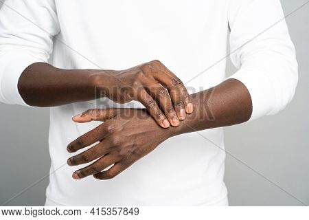 Closeup Of African Man Arms Touching Painful Wrist Caused By Prolonged Work On Computer, Laptop. Bla