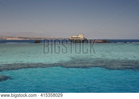 The Sunken Shipwreck On The Reef, Tiran Island, Egypt, Red Sea. Old Rusty Wreckage Of A Cargo Ship O