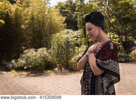 Caucasian Woman With Black Turban With A Relaxed Face And With Her Hands On Her Heart
