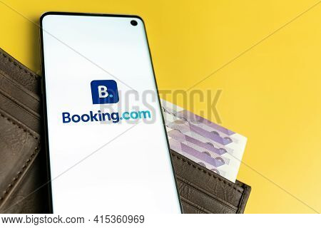 Swansea, Uk - March 28, 2021: Booking.com App Logo Displayed On Smartphone On Brown Wallet With Cash