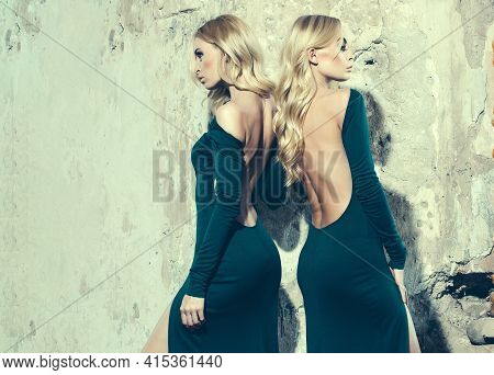 Young Women With Long Lush Curly Blonde Hair And Thoughtful Face In Fashion Dress Standing Near Ston