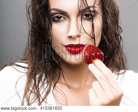 Young Sexy Woman With Sexy Red Lips On Pretty Face And Wet Hair Holding Strawberry Berry Fruit