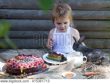 Cute Baby Boy In White Pinafore And Little Rabbit At Table Served With Fruit Cake And Cup Of Milk Ou