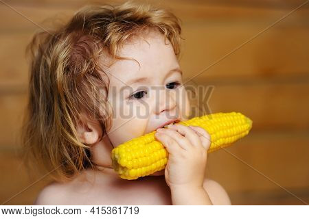 Baby Eating Yellow Corn Or Maize With And Funny Face On Wooden Background