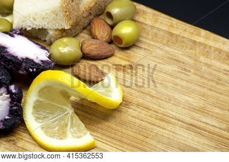 Cheeses, Lemon, Nuts And Olives On Light Wooden Cutting Board. Serving Antipasto On Older Wooden Cho