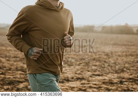 Man in stretchy hoodie in the countryside at sunset