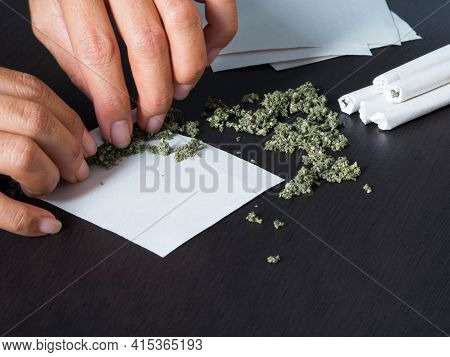 Over Light Of Marijuana Joints With Hand Hemp Roll On Black Wood Background. Narcotic Recreational D