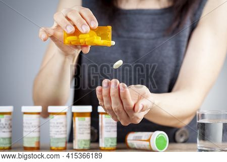 A Young Caucasian Woman Is Taking A Pill Out Of The Medication Bottle. She Has A Stack Of Bottles Li
