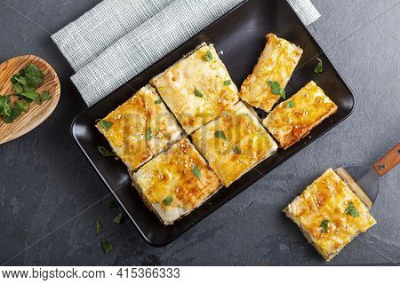 Turkish Kiymali Borek Served On A Tray After Being Sliced Into Square Shapes. Fresh Parsley Leaves A