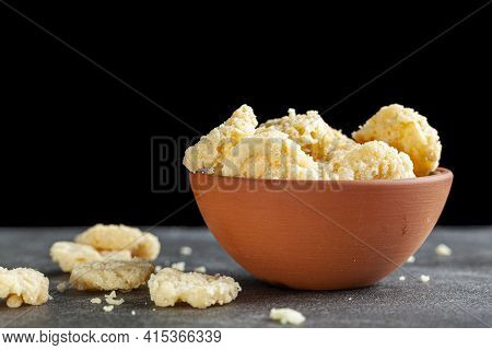 Oven Baked Cheese Bites In A Terra Cotta Cup Against Dark Background. These Crunchy Delicious Snacks