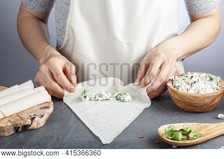 A Caucasian Woman Is Filling Phyllo Dough Sheets Known As Yufka With Cheese Stuffing To Make Traditi