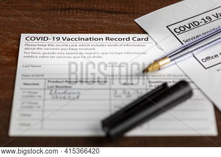 Close Up Isolated Image Of A Covid 19 Vaccination Record Card On A Wooden Desk. The Card Details The