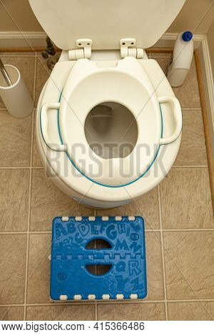A Child Toilet Seat Attachment Placed On Top Of A Toilet For A Kid During Potty Training. A Step Pla