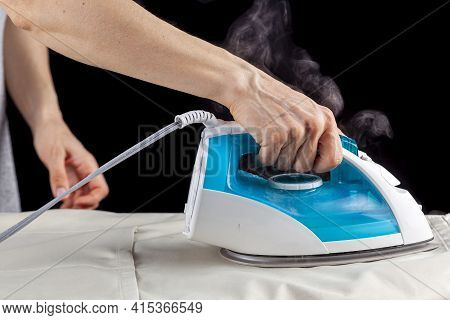 Close Up Isolated Image Of A White Woman Ironing A Cloth On An Ironing Board. Hot Steam Is Coming Ou
