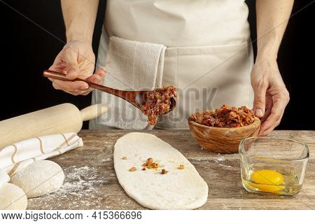 A Turkish Woman Is Preparing Kiymali Pide, Traditional Flatbread With Ground Meat Paste Onto Flatten