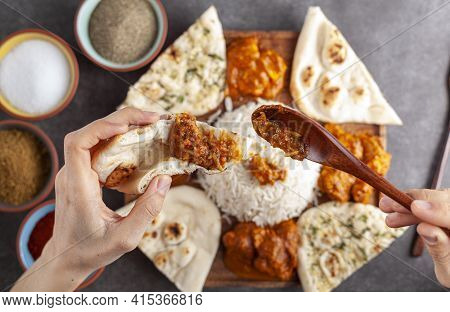 Flat Lay Image Of A Woman Putting Chicken Tikka Masala On A Slice Of Naan Bread With A Platter Of Tr