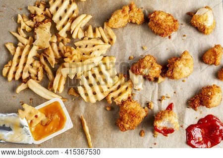 Flat Lay Image Of A Messy Food With Waffle Fries And Chicken Nuggets On Baking Paper Together With K