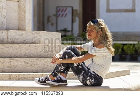 Tomar, Portugal 07-11-2010: Mutton Dressed As Lamb Blonde Woman In Her Forties Is Sitting Alone On T