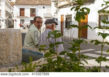 09-07-2010 Ronda, Spain: Two Elderly Spanish Men Are Sitting On A Stone By A Fountain At The Town Ce