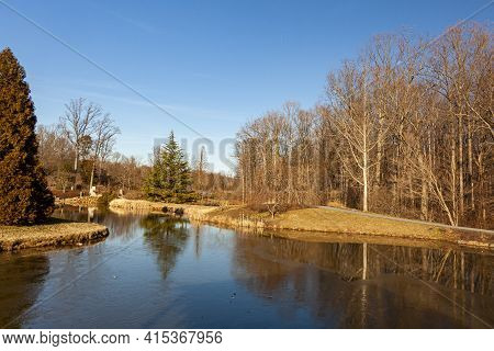 View Of A Scenic Park At An Afternoon In Late Autumn With Naked Trees, A Grassland, Hiking Trail, An