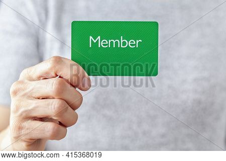 A Young Caucasian Woman Is Holding A Green Card That Says Member On It. A Customizable Image Which H