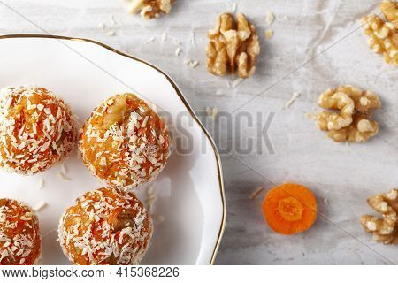 A Flat Lay Of Kitchen Countertop With A Flat Porcelain Plate. Homemade Fresh Carrot Bliss Balls (mix