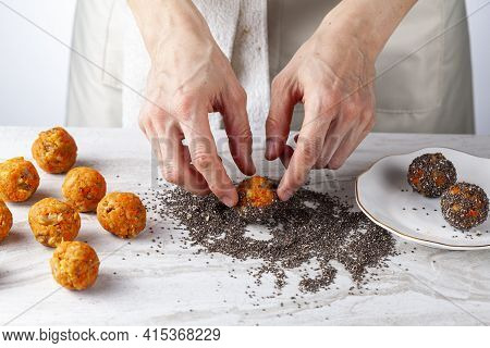 A Woman Chef Is Preparing Carrot Cake Bliss Bites In The Kitchen. She Dips The Carrot Balls Into A P