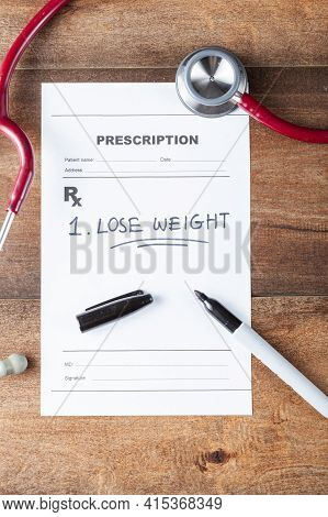 Close Up Flat Lay Image Of A Doctor's Office Desk With A Stethoscope, Pen And A Prescription That Ha