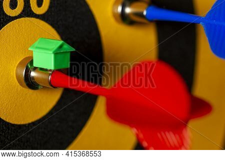 A Dart Board With An Arrow Hitting The Bullseye. There Is A Small House Icon On Top Of That Arrow. A