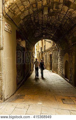 Barcelona, Spain 05-01-2010: A Couple Holding Hands In Carrer De La Volta Del Remei,  Narrow Stone A