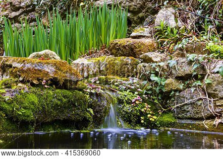 A Close Up Look At A Tiny Waterfall As Part Of A Decorative Garden Pond Surrounded With Mossy Rocks,