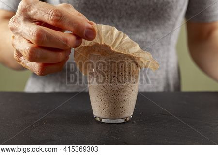 A Woman Is Carefully Removing The Top Cover Of A Sourdough Starter Culture Which Is About To Overflo