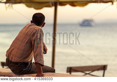 A Jordanian Man Wearing Long Sleeve Shirt Is Sitting On A Wall By The Beach In Aqaba, Jordan. He Is