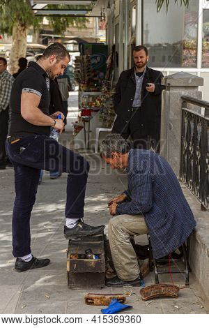 Hama, Syria 04-02-2010: An Elderly Syrian Shoe Shiner Is Polishing A Young Man's Shoes On His Shoesh